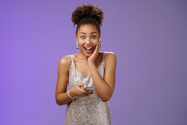 Mulher afro-americana bonita e animada, surpresa, em um vestido brilhante de prata, toque a palma da mão espantada, arregalar os olhos, impressionado, soltar a mandíbula ofegante segurando smartphone atônito receber boas notícias.