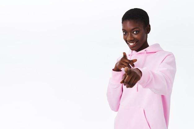Mulher afro-americana, bonita e atrevida com cabelo curto em um elegante moletom rosa com capuz, apontando para você, convidando para o evento, sorrindo e parecendo animada