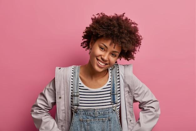 Mulher afro-americana bonita e charmosa inclina a cabeça, sorri gentilmente, desfruta de um momento agradável na vida, usa macacão jeans e anoraque, está de bom humor, posa sobre uma parede em tom pastel rosado