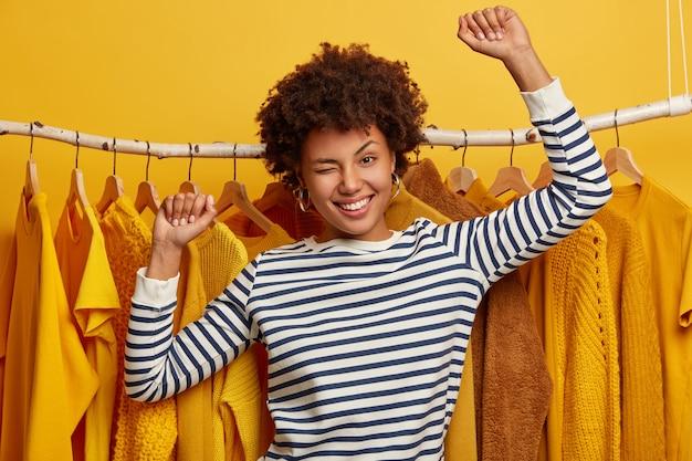 Mulher afro-americana bonita e enérgica pisca os olhos, dança, usa um macacão striprd, fica de pé contra as barras de roupas, compra roupas novas