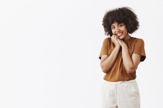 Mulher afro-americana bonita e tocante com cabelo encaracolado em uma camiseta marrom inclinando a cabeça e apoiando-se nas mãos sorrindo com expressão encantada e satisfeita olhando com carinho