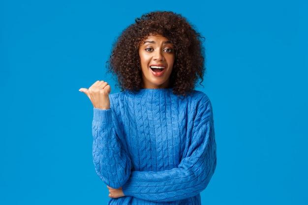 Mulher afro-americana bonita feliz animada com corte de cabelo afro na camisola de inverno, apontando o polegar para a esquerda e rindo como discutir momento engraçado, conversando casualmente durante a festa, parede azul