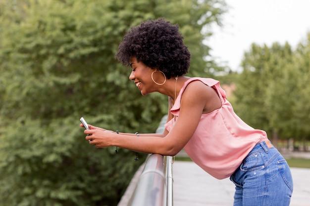 Mulher afro-americana bonita nova feliz que sorri e que usa o telefone móvel. fundo verde primavera ou verão. roupa casual ao ar livre