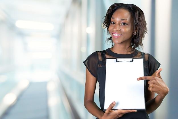 Mulher afro-americana bonita nova que mostra a prancheta com espaço da cópia