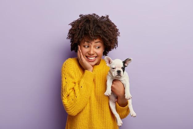 Mulher afro-americana brincalhona feliz por comprar filhote de cachorro com pedigree