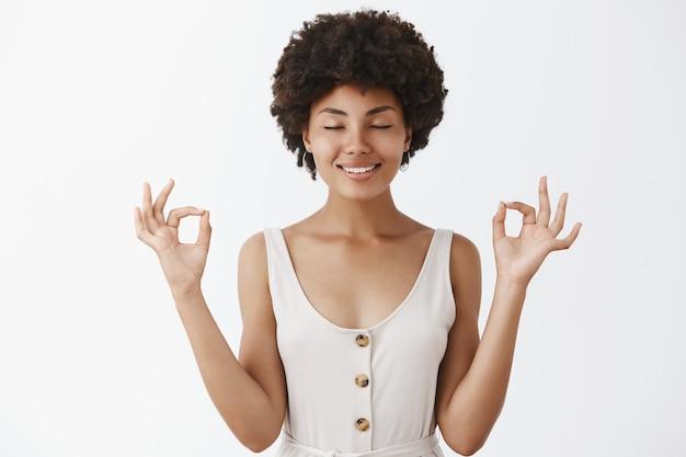 Mulher afro-americana calma e relaxada, de boa aparência, feliz e aliviada com roupas da moda, fechando os olhos e sorrindo, segurando as mãos levantadas em um gesto zen, meditando