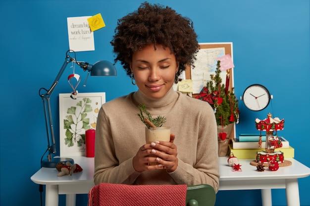 Mulher afro-americana calma e relaxada posa com coquetel de gemada, senta-se na cadeira com os olhos fechados e usa uma blusa de gola olímpica marrom