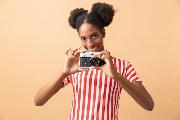 Mulher afro-americana cândida sorrindo e fotografando na câmera retro, isolada