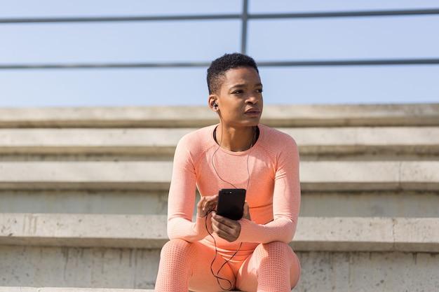 Mulher afro-americana cansada depois do treino, ouvindo música e podcast de áudio, depois de correr e treinar no estádio pela manhã
