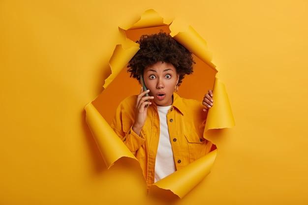 Mulher afro-americana carismática impressionada em pé no fundo do buraco de papel