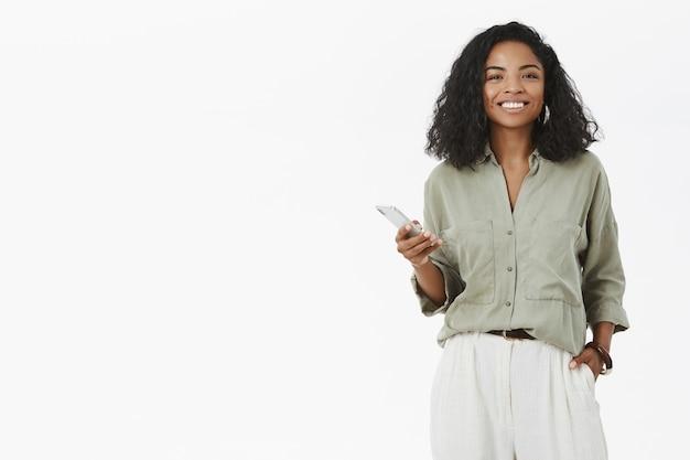 Mulher afro-americana charmosa carismática com penteado encaracolado segurando a mão no bolso usando smartphone
