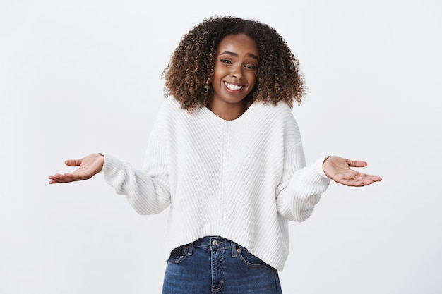 Mulher afro-americana charmosa e despreocupada, sorrindo, penteado encaracolado, encolhendo os ombros com as mãos estendidas para os lados, parece despreocupado, sem dar interesse, parado sem noção, parede branca inconsciente