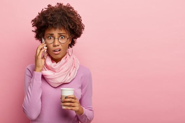 Mulher afro-americana chocada e estressada fala por telefone celular, segura café para viagem, ouve más notícias, usa óculos e poloneck roxo, posa sobre a parede rosada do estúdio.