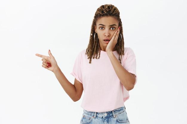 Mulher afro-americana chocada e preocupada ofegando, apontando o dedo para a esquerda