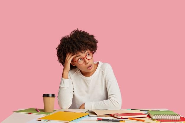 Mulher afro-americana chocada usa óculos, vestida com roupas brancas, trabalha na inicialização da criação,