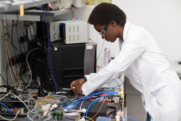 Mulher afro-americana cientista que trabalha em laboratório com tecnologia eletrônica. pesquisa e desenvolvimento de dispositivos eletrônicos por mulher negra de cor.