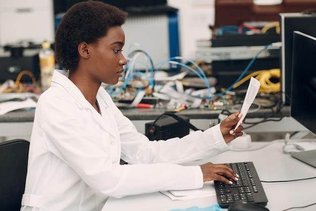 Mulher afro-americana cientista, trabalhando em laboratório com computador e digitando texto científico rese ...