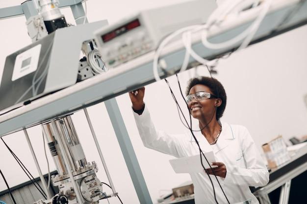 Mulher afro-americana cientista trabalhando em laboratório com detector de fóton único de tecnologia eletrônica r ...