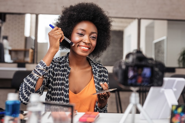 Mulher afro-americana com cabelo encaracolado com aparência positiva durante a gravação de vídeo