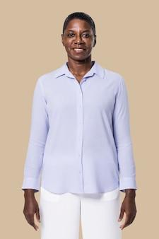 Mulher afro-americana com camisa azul de manga comprida e calça branca