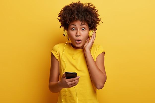 Mulher afro-americana com camiseta amarela e fones de ouvido