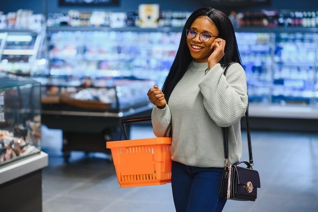 Mulher afro-americana com carrinho do carrinho de compras na loja do supermercado falar no celular.