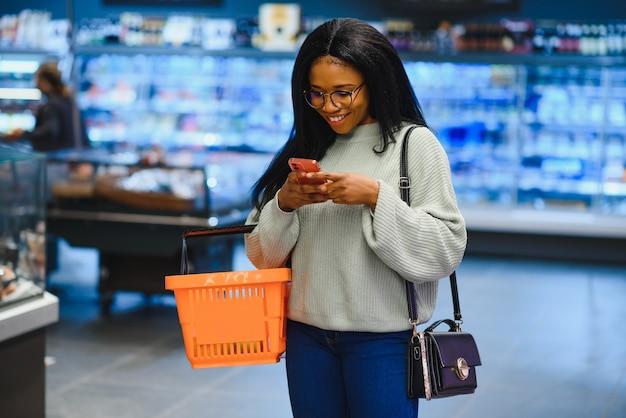 Mulher afro-americana com carrinho do carrinho de compras na loja do supermercado olha no celular.