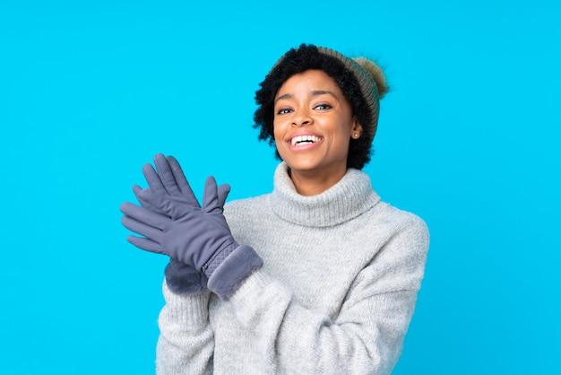 Mulher afro-americana com chapéu de inverno isolado parede azul