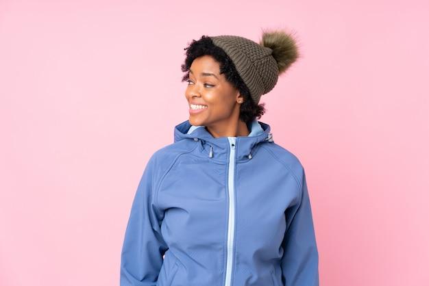 Mulher afro-americana com chapéu de inverno isolado parede rosa
