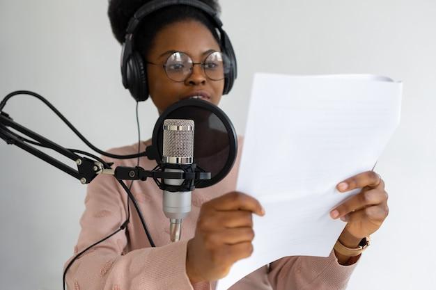 Mulher afro-americana com fones de ouvido e um microfone gravando um podcast em um estúdio de gravação