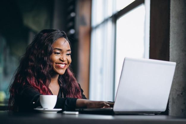 Mulher afro-americana com laptop e café
