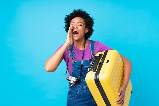 Mulher afro-americana com mala amarela sobre parede azul isolada