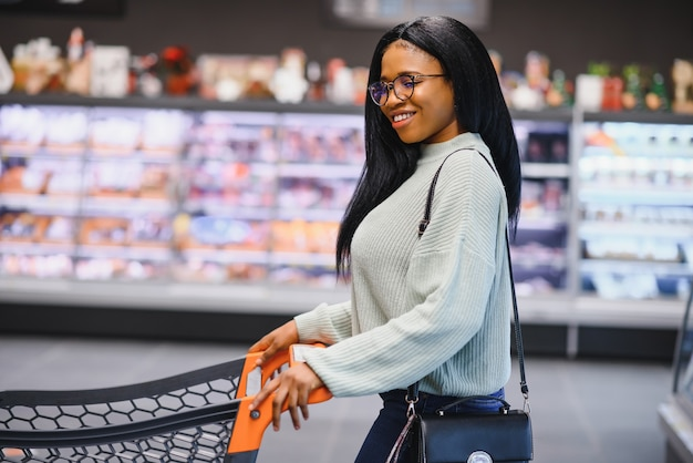 Mulher afro-americana com o carrinho do carrinho de compras na loja do supermercado.