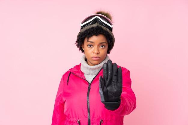 Mulher afro-americana com óculos de esqui sobre parede rosa isolada