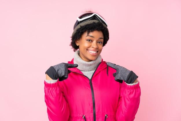 Mulher afro-americana com óculos de neve sobre parede rosa