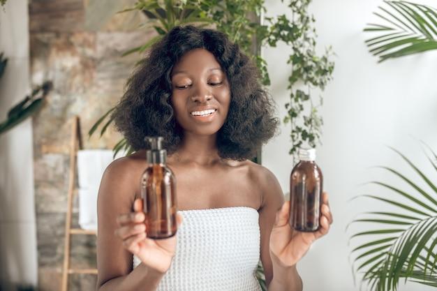 Mulher afro-americana com ombros nus e produtos cosméticos