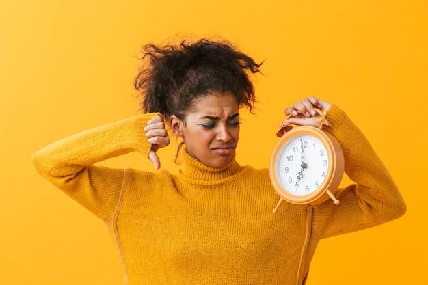 Mulher afro-americana com sono em roupas casuais franzindo a testa enquanto segura o despertador, isolado