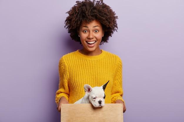 Mulher afro-americana com suéter amarelo segurando cachorro
