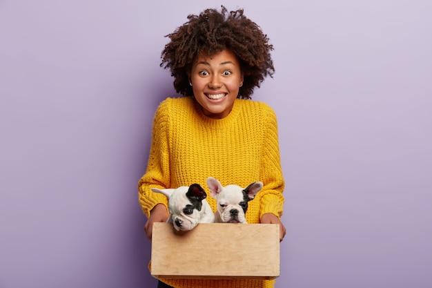 Mulher afro-americana com suéter amarelo segurando filhotes
