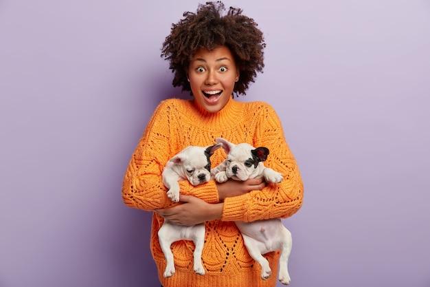 Mulher afro-americana com suéter laranja segurando filhotes