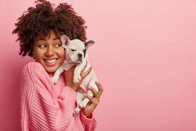 Mulher afro-americana com suéter rosa segurando um cachorrinho