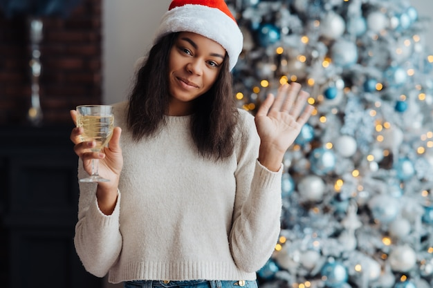 Mulher afro-americana com taça de champanhe em casa. celebração do natal