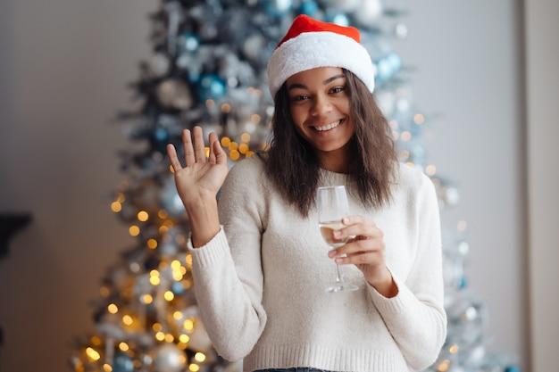 Mulher afro-americana com taça de champanhe em casa