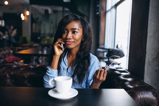 Mulher afro-americana com telefone em um café