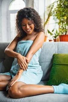 Mulher afro-americana com toalha, fazendo sua rotina diária de cuidados com a pele em casa.