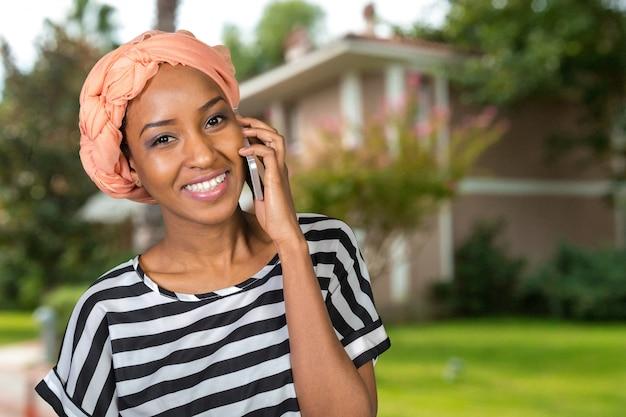 Mulher afro-americana com um telefone móvel