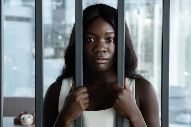 Mulher afro-americana com uma expressão triste atrás das barras de ferro