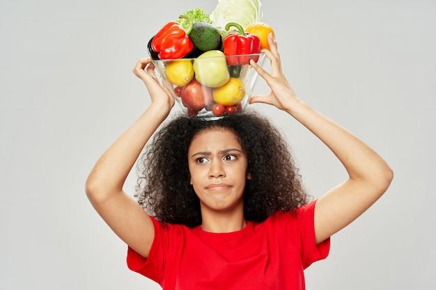 Mulher afro-americana com uma tigela de legumes na cabeça