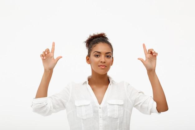 Mulher afro-americana confiante apontando para cima