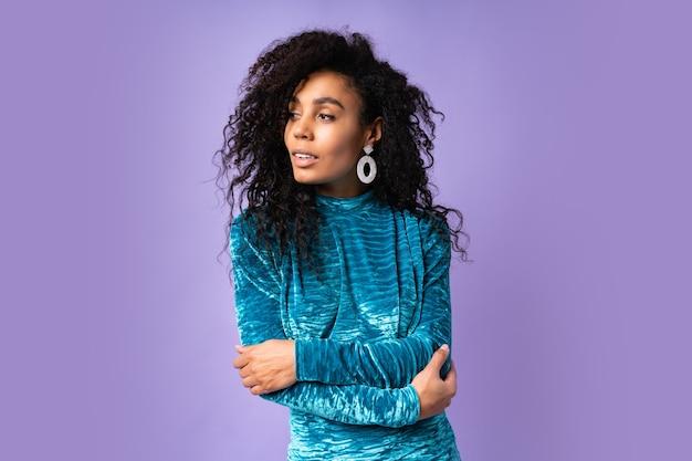 Mulher afro-americana confiante num vestido de veludo com cabelos ondulados posando. retrato do estilo da moda.